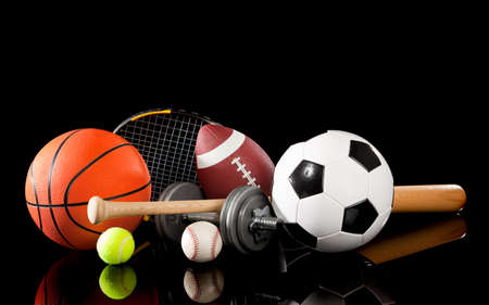 racket sport: Equipos de deportes surtido incluyendo una pelota de baloncesto, bal�n de f�tbol, pelota de tenis, b�isbol, murci�lago, raqueta de tenis, f�tbol y pesas sobre un fondo negro Foto de archivo