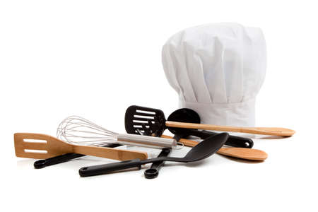 A white chefs toque with various cooking utensils including a wisk, wooden spoons, spatulas on a white background