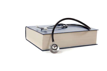reference book: Un libro de referencia m�dico con un estetoscopio sobre un fondo blanco  Foto de archivo