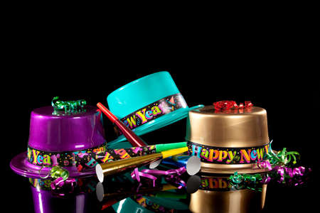 Colored New Years Eve hats including green, purple, pink gold and red, streamers, noise makers and confetti on a black background