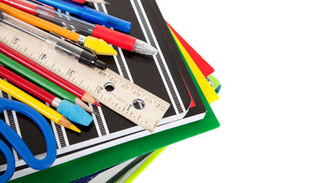 School Supplies including notebooks, composition books, ruler, pencils, erasers, scissors, pens and folders on a white background with copy space photo