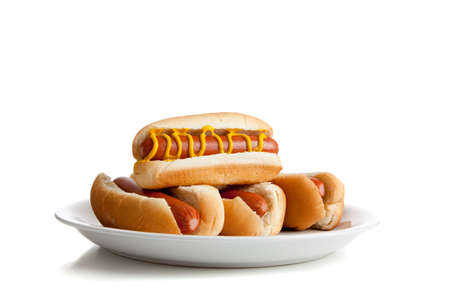 perro caliente: Perros calientes apilados con mostaza y mo�os en un plato y un fondo blanco