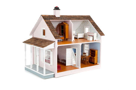 miniatures: a furnished pink doll house on a white background