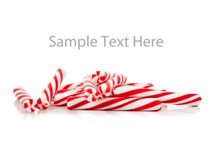 Red and white striped candy canes on a white copy space Imagens