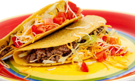 Two tacos with beef, lettuce, tomato and cheese on a plate on white background photo