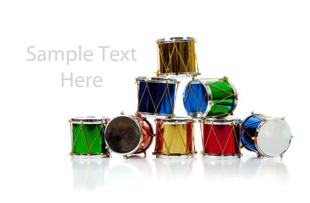 Assorted colored miniature Christmas drums including red, gold, green and blue on  a white background with copy space