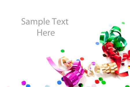 Multi-colored confetti and streamers including gold, red, green and purple on a white background with copy space