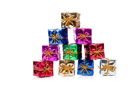 Assorted colored miniature Christmas presents including purple, red, gold, green and blue on  a white background photo