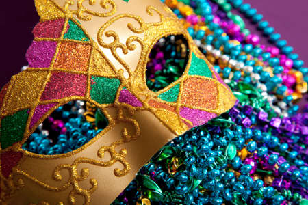 A background made up of a gold mardi gras mask and blue, purple, green and pink beads