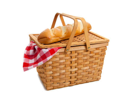 A wicker picnic basket with french bread on a white background photo