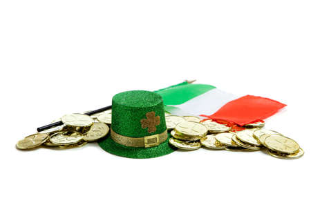 St. Patricks day decorations including gold coins, green glittery leprecaun hat and irish flag on a white background photo
