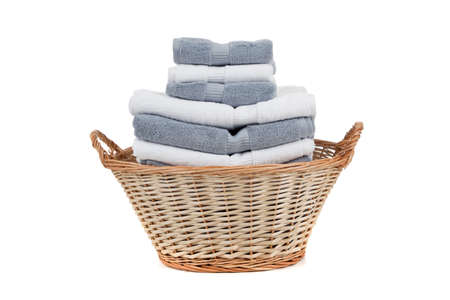 dirty clothes: A wicker laundry basket full of white and gray towels on a white background