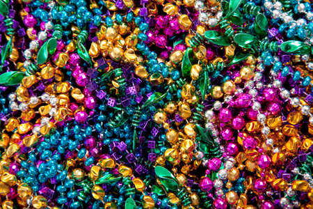 colorful beads: A background of colorful mardi gras beads including gold, blue, green, pink and purple Stock Photo