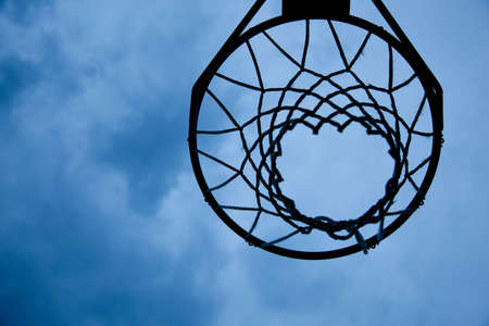 A basketball hoop and net with a blue sky background with copy space photo