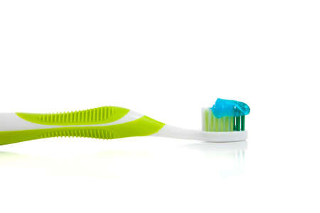 a lime green toothbrush and blue gel toothpaste on a white background