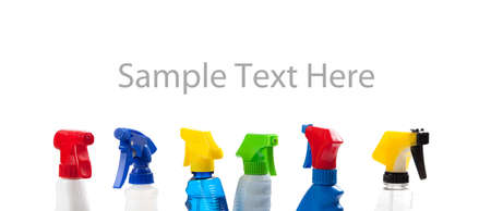 triggers: a row of Assorted colored cleaning bottle with triggers including red, blue, yellow, white, black and green with copy space Stock Photo