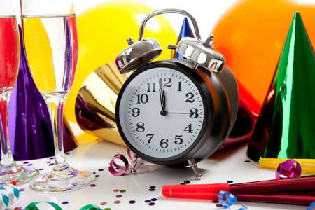 Assorted New Year's Eve party supplies including party hats, balloons, clock, noise makers, confetti, streamers, champagne Foto de archivo
