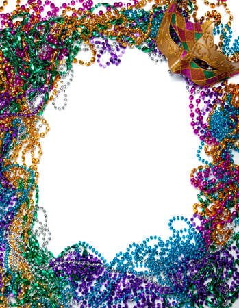 masquerade masks: A border made of a gold, purple and green mardi gras mask and blue, green, red, gold and purple plastic beads Stock Photo