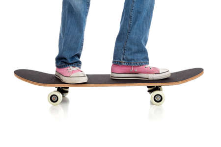 A girls legs in jean and pink sneakers riding a skateboard on a white background photo