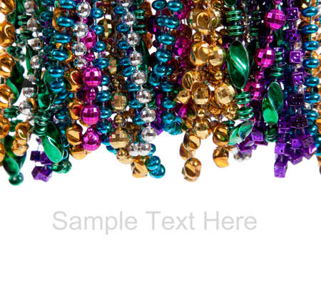 mardi: Multi colored mardi gras beads including blue, green, purple, pink, yellow and gold on a white background with copy space