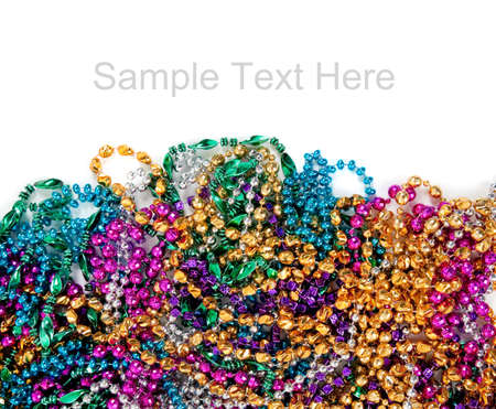Multi colored mardi gras beads including blue, green, purple, pink, yellow and gold on a white background with copy space photo