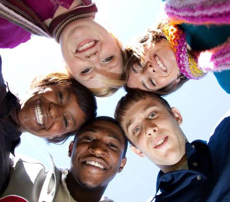 Een groep van lachende gezichten van multiraciale studenten buiten met de blauwe lucht op de achtergrond