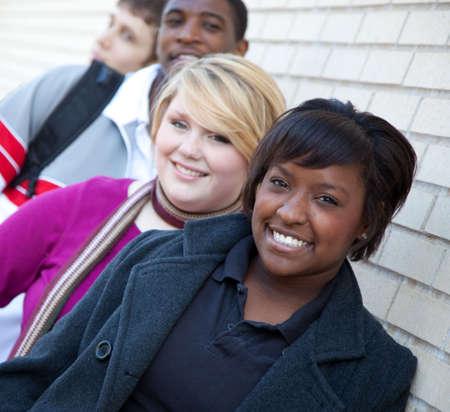 Multiraciale studenten buiten tegen een bak stenen muur Stockfoto