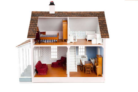 A Childs doll house with furniture on a white background