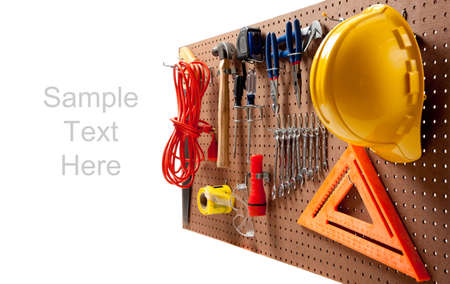 Peg board with hardhat, extension cord, flashlight, hammer, screw driver, caution tape, carpenters square and pliers