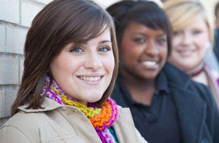 multi race: Un grupo de estudiantes de la Universidad femenina de multirraciales fuera contra una pared de ladrillo