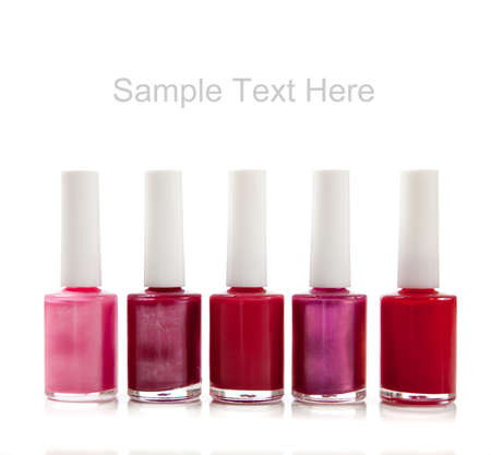 nail polish bottle: Assorted fingernail polish including red, purple  and pinks on a white background with copy space Stock Photo