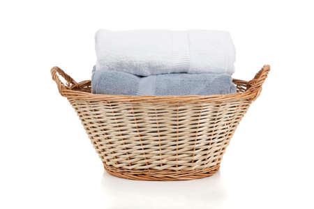 White and blue towels in a wicker laundry basket on a white background