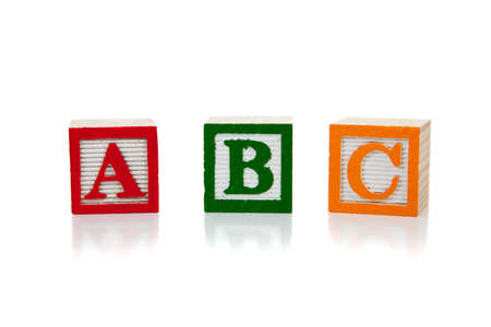 abc's: Colored wooden letter blocks including red, green and yellow on a white background with copy space