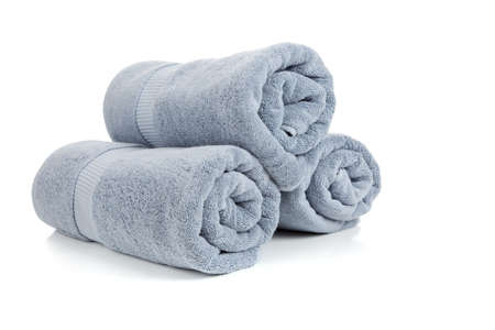 absorb: Three rolled gray towels on a white background