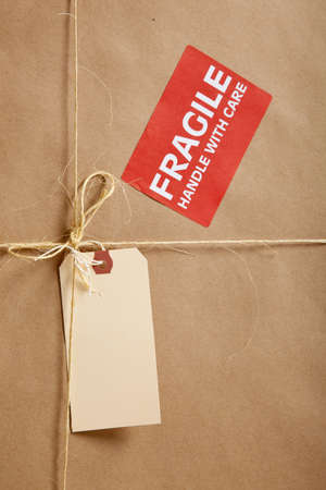 A cardboard box background with Blank shipping label and twine  Reklamní fotografie