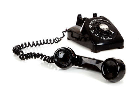 A vintage black telephone  with a white background photo