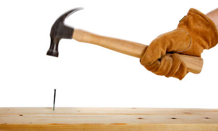 construction nails: A leather gloved hammering a nail in a two by four on a white background