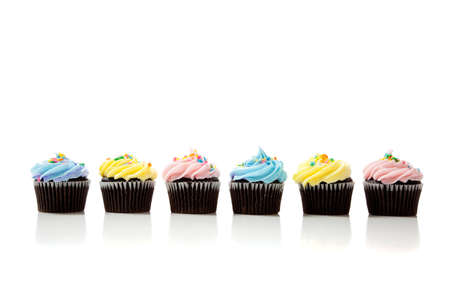 Pastel cupcakes including blue, pink and yellow on a white background with copy space Stock Photo - 6756460