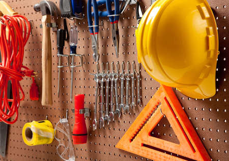 peg board: Peg board with hardhat, extension cord, flashlight, hammer, screw driver, caution tape, carpenters square and pliers