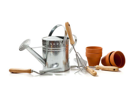 Assorted gardening supplies including watering can, pots, spade, shovel and cultivator on a white background