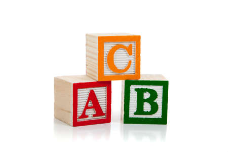 block letters: Colored wooden letter blocks including red, green and yellow on a white background with copy space