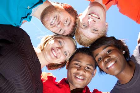 Un groupe de sourire des étudiants du Collège multiraciales en dehors avec le ciel bleu en arrière-plan  Banque d'images