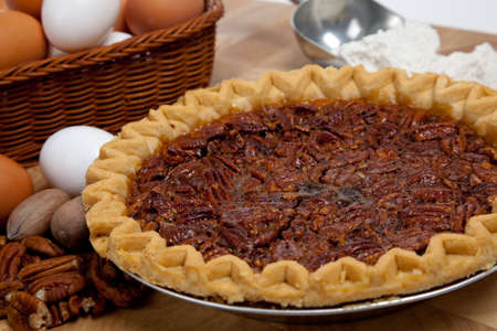 A homemade pecan pie with pecans, white and brown eggs and scoop of flour