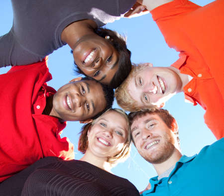 multi race: Un grupo de sonrientes rostros de los estudiantes de colegio multirraciales fuera con el cielo azul en el fondo  Foto de archivo