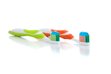 green and orange toothbrushes with a white background Banco de Imagens
