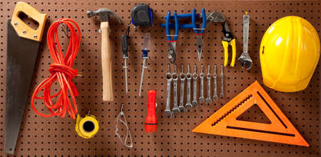 the screw driver: Peg board with hardhat, extension cord, flashlight, hammer, screw driver, caution tape, carpenters square and pliers