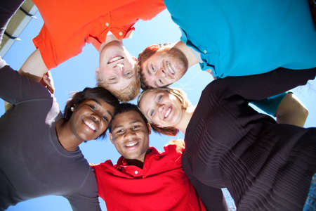 A group of smiling faces of multi-racial college students outside with the blue sky in the background