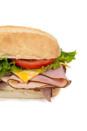 hoagie: A ham and tureky sandwich on a hoagie bun with lettuce, tomato and cheese on a white background