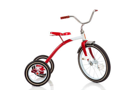 A childs red tricycle on a white background photo
