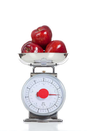 scales thin: Three red apples on a food scale on a white background